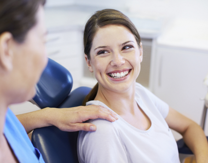 a smiling patient with a doctor's hand on her shoulder